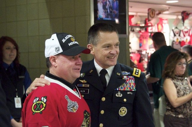Gen. Daniel B. Allyn, commanding general of U.S. Army Forces Command, poses with a Chicago Blackhawks fan before Game 1 of the Stanley Cup Finals June 12, 2013 in Chicago's United Center. Allyn, visiting the city to highlight veterans' service as well as the Army's 238th birthday, was recognized alongside other U.S. military veterans during the game. (U.S. Army photo by Dave Chace, FORSCOM Public Affairs)
