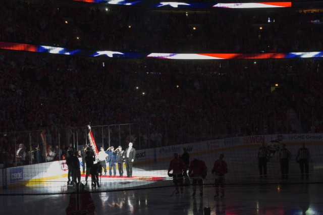 From left within the spotlight, U.S. Army and Marine Corps veteran Michael Pamonicutt , U.S. Navy veteran Ray Morley and Gen. Daniel B. Allyn, commanding general of U.S. Army Forces Command, honor the U.S. colors during the national anthem to kick off Game 1 of the Stanley Cup Finals June 12, 2013 in Chicago. Allyn, representing the U.S. Army, is visiting the city to highlight U.S. Army veterans' service and commitment to their communities as well as the Army's 238th birthday. The singer, Jim Cornelison, has been singing the national anthem for the Chicago Blackhawks since 1996. (U.S. Army photo by Dave Chace, FORSCOM Public Affairs)