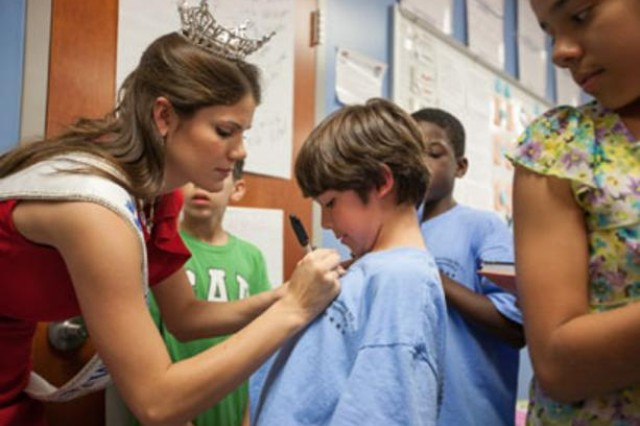 Miss Maryland Joanna Guy signs her autograph on fifth-grader Joseph Whipkey's shirt during her visit to Pershing Hill Elementary School. Guy signed autographs and answered questions about her reign.