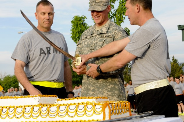 """FORT CARSON, Colo. -- Col. (P) John """"J.T."""" Thomson, deputy commander, 4th Infantry Division and Fort Carson, and Command Sgt. Maj. Brian M. Stall, senior enlisted advisor, 4th Inf. Div. and Fort Carson, cut a cake in celebration of the Army's 238th Birthday with the most junior Soldier Pvt. Lorence Vigil, Abrams armored crewmember, Company D, 1st Battalion, 68th Armor Regiment, 3rd Armored Brigade Combat Team, 4th Inf. Div., June 13, 2013, at Founders Field. """"Cut the table in half"""" Thomson instructed Vigil."""