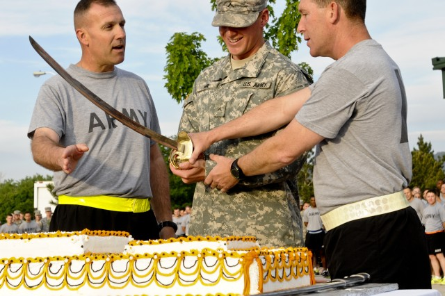 """FORT CARSON, Colo. -- Col. (P) John """"J.T."""" Thomson, deputy commander, 4th Infantry Division and Fort Carson, and Command Sgt. Maj. Brian M. Stall, senior enlisted advisor, 4th Inf. Div. and Fort Carson, cut a cake in celebration of the Army's 238th Birthday. with the most junior Soldier, Pvt. Lorence Vigil, Abrams armored crewmember, Company D, 1st Battalion, 68th Armor Regiment, 3rd Armored Brigade Combat Team, 4th Inf. Div., June 13, 2013, at Founders Field. """"Cut the table in half"""" Thomson instructed Vigil."""