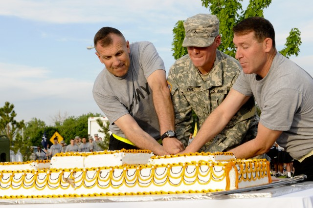 """FORT CARSON, Colo. -- Col. (P) John """"J.T."""" Thomson, deputy commander, 4th Infantry Division and Fort Carson, and Command Sgt. Maj. Brian M. Stall, senior enlisted advisor, 4th Inf. Div. and Fort Carson, cut a cake in celebration of the Army's 238th Birthday, with the most junior Soldier, Pvt. Lorence Vigil, Abrams armored crewmember, Company D, 1st Battalion, 68th Armor Regiment, 3rd Armored Brigade Combat Team, 4th Inf. Div., June 13, 2013, at Founders Field. """"Cut the table in half"""" Thomson instructed Vigil."""