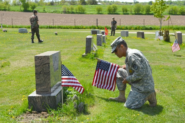 Sgt. 1st Class Allan Welchez, a chief food management NCO assigned to 10th Sustainment Brigade, replaces American flags at a cemetery in Lowville, in honor of fallen heroes on Memorial Day. He takes time to volunteer as much as he can while still being able to spend time with his Family and serve his country with pride.