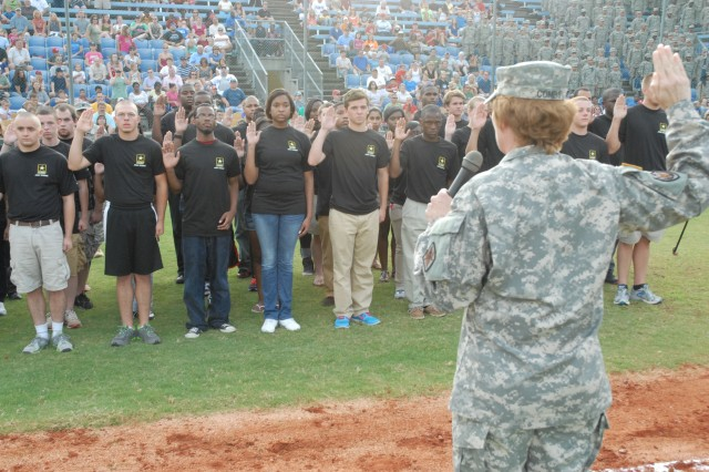 Brig. Gen. Peggy Combs, Fort Jackson's commanding general, leads Army recruits in the oath of enlistment during the game.