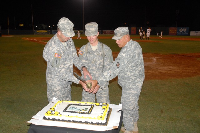 Col. Stephen Yackley, left, Fort Jackson's deputy commanding officer; and Post Command Sgt. Maj. Kevin Benson, right, help Pvt. Joseph Huziak, 3rd Battalion, 13th Infanftry Regiment, with the cutting of the Army birthday cake during the seventh-inning stretch.