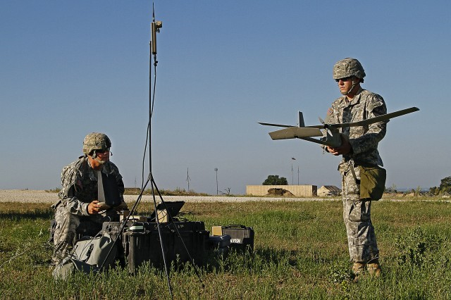 """Staff Sgt. Bo Baker (left), an electronic warfare specialist, and, Cpl. Kristopher Tive, an intelligence analyst, both assigned to Headquarters and Headquarters Company, 115th """"Muleskinner"""" Brigade Support Battalion, 1st """"Ironhorse"""" Brigade Combat Team, 1st Cavalry Division, conduct pre-flight checks prior to launching a Raven, an unmanned aerial surveillance vehicle, during the Brigade Support exercise June 4, at Fort Hood, Texas. The checks ensure proper and safe operation of the Raven during flight."""