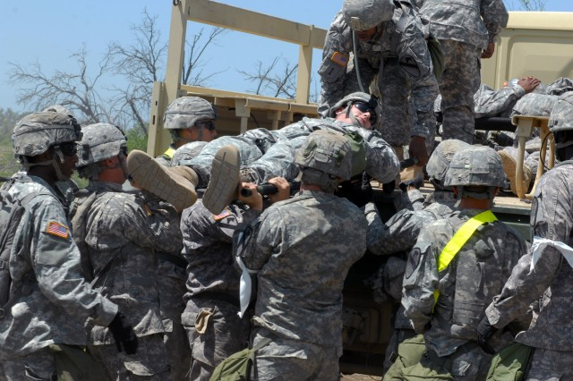 """Soldiers assigned to the 1st """"Ironhorse"""" Brigade Combat Team, 1st Cavalry Division, unload a simulated-casualty from a military vehicle while conducting a mass casualty exercise during the Brigade Support Areas exercise June 6, at Fort Hood, Texas. The exercise allows medics to practice life-saving skills during a rapid influx of casualties with varying wounds."""