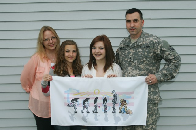 The Brady Family displays a replica of Sabrina Brady's winning entry in the U.S. Doodle4Google contest. Pictured (left to right) are April, Brittan, Sabrina and Master Sgt. Bryce Brady.