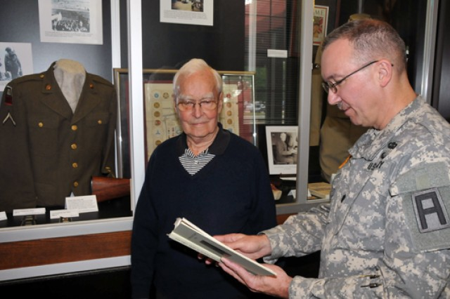 Emmett Keenan and First Army Chaplain, Lt. Col. Timothy Bedsole, flip through the 'First Army In Europe' book during his visit to First Army Headquarters June 6, 2013, the 69th anniversary of D-Day. Keenan served with the 745th Tank Battalion during D-Day and was attached to the 1st Infantry Division and First Army.