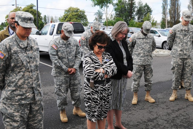 Soldiers and civilian staffers of the 364th Expeditionary Sustainment Command observe a moment of silence during the dedication of the unit's new Gold Star Families parking space, June 13.