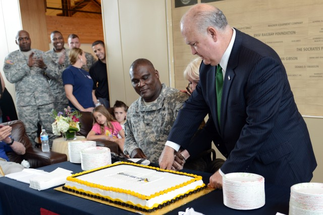 Under Secretary of the Army Joseph W. Westphal cuts the Army birthday cake with Col. Gregory Gadson, commander of Fort Belvoir, Va., and (behind Westphal) CEO and president of the USO of Metropolitan Washington, Elaine Rogers.
