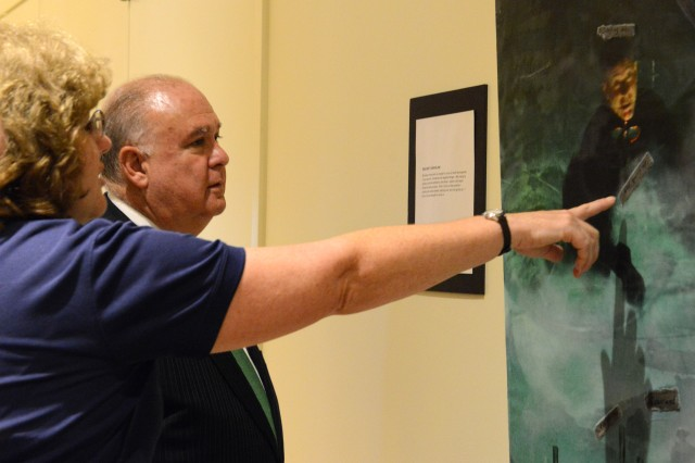 Under Secretary of the Army Joseph W. Westphal looks at a piece of art done by a wounded warrior, as he tours the newly built USO Warrior and Family Center at Fort Belvoir, Va., June 13, 2013.