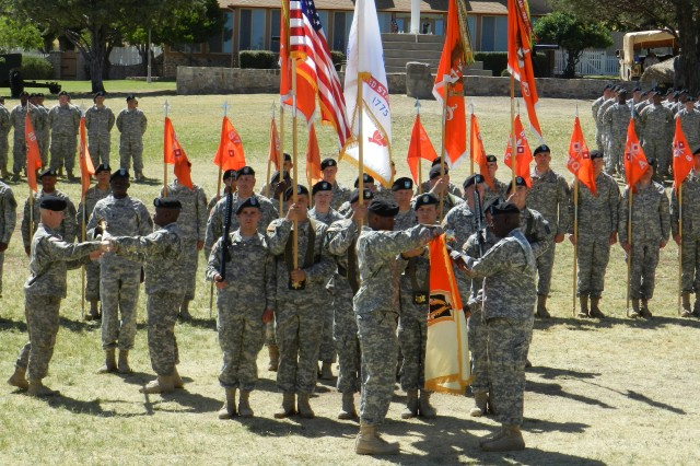 1st Lt. Alex Bridgeforth ,far left, and 1st Sgt. Daniel Stewart ,far right, the company command team and Col. James Parks, III ,right, and Command Sgt. Maj. Maurice Rambert ,left, the brigade command team for Headquarters and Headquarters Company, 11th Signal Brigade, case their respective colors in preparation for the brigade headquarters' relocation to Fort Hood, Texas. during the 11th Sig. Bde. change of command and color-casing ceremony on June 7 on Brown Parade Field.