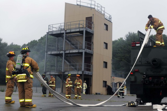 U.S. Soldiers with the 287th, 339th, 356th, and 530th Engineer Firefighting Teams as well as the Headquarters Company, 468th Engineer Detachment prepare hoses as part of a controlled burn training exercise in Bedford, Mass, June 8, 2013.