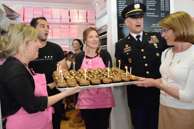 Sgt. Maj. of the Army Raymond F. Chandler III, his wife Jeanne Chandler, and the owners of Georgetown Cupcake, sisters (left) Sophie LaMontagne and Katherine Berman, sing 'Happy Birthday' during an event for the Army birthday, at the cupcake shop in Washington, D.C., June 14, 2013.