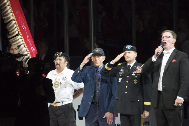 From left, U.S. Army and Marine Corps veteran Michael Pamonicutt , U.S. Navy veteran Ray Morley and Gen. Daniel B. Allyn, commanding general of U.S. Army Forces Command, honor the U.S. colors during the national anthem to kick off Game 1 of the Stanley Cup Finals June 12, 2013 in Chicago. Allyn, representing the U.S. Army, is visiting the city to highlight U.S. Army veterans' service and commitment to their communities as well as the Army's 238th birthday. The singer, Jim Cornelison, has been singing the national anthem for the Chicago Blackhawks since 1996. (U.S. Army photo by Dave Chace, FORSCOM Public Affairs)
