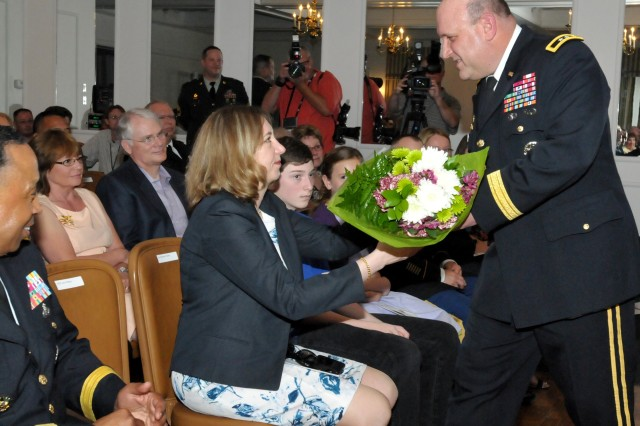 Maj. Gen. John Wharton presents his wife, Rebekah, with a bouquet of flowers as a symbolic gesture of his thanks for her support during his Army career. Wharton also presented a bouquet of flowers to his daughter and a card to his son. (Photo by Jon Micheal Connor, ASC Public Affairs)