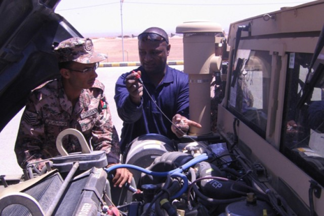 Rickey Mitchell (right), a member of a technical assistance field team, trains a Jordanian soldier on vehicle maintenance. Mitchell's Army knowledge and experience with high mobility artillery rocket systems qualified him for a contract to assist the Jordanian artillery battalion in its transition to HIMARS. He is currently employed by Loyal Source Government Services, based in Orlando, Fla.