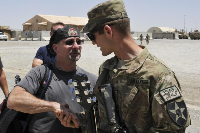 Bart Davis, a guitar player with the U2 tribute band L.A.vation, shakes hands with 2nd Lt. Sean D. Fiorrella, from Katy, Texas, with 2nd Battalion, 23rd Infantry Regiment after borrowing Fiorrella's guitar for an impromptu show June 6, 2013 at Forward Operating Base Spin Boldak, Afghanistan. The band was touring with other entertainers and celebrity chefs as part of Operation Honor Our Troops. (U.S. Army photo by Staff Sgt. Shane Hamann, 102nd Mobile Public Affairs Detachment.)