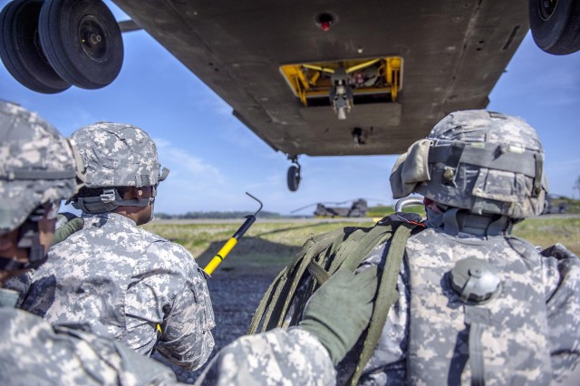 Students and instructors stand ready to hook-up to the approaching CH 47D Chinook. The 593rd Sustainment Brigade graduated 32 students from a sling load inspector certification course, May 10. (Photo by Sgt. Mark A. Cloutier)
