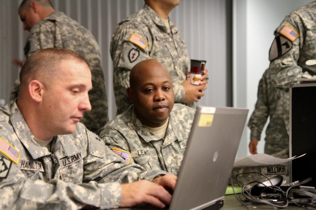 Sgt. 1st Class Clinton Hamilton, a Las Vegas native, and targeting non-commissioned officer-in-charge, and Chief Warrant Officer 2 Alfredo Lewis, a Monroe, La., native, and operations targeting officer, both with Headquarters and Headquarters Battery, 17th Fires Brigade, discuss and refine their targeting analysis during a staff exercise at the Mission Command Training Complex, Joint Base Lewis-McChord, Wash., June 5, 2013. (U.S. Army photo by Spc. Nathan Goodall, 17th Fires Bde. Public Affairs)