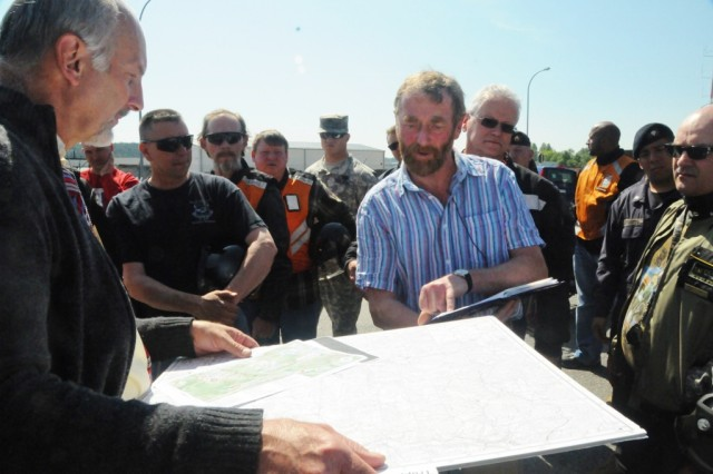 Steve Foster (center) and Norbert Wittl (left) use maps and old photos to pinpoint the exact location of Stalag 383 in what is now the Hohenfels training area.