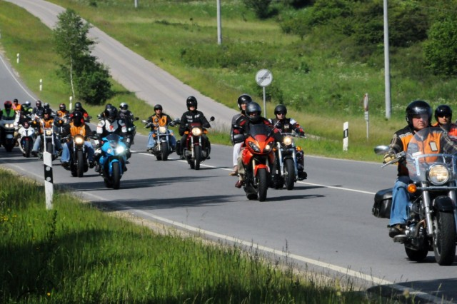 A group of Hohenfels motorcycle enthusiasts escort Steve Foster and his wife Chris onto post in search of his father's past, June 13.