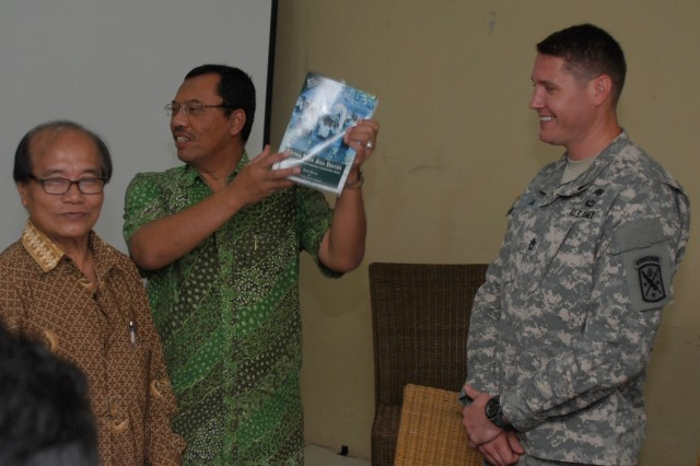 Dr. Mulyaman Soepardi, the founder and funder of the School of Industrial Technology and Pharmacy (middle), holds up one of the medical books donated to the school in Bogor, Indonesia on June 17. Indonesian and U.S. Army Soldiers, such as Sgt. 1st Class Arturo Balsa (right), coordinated the donation of 300 books, which are expected to help the students treat and educate residents of 60 villages around Bogor. Soepardi, Balsa, and school Director Dr. Padmono Citroreksoko (left) spoke at the donation ceremony.