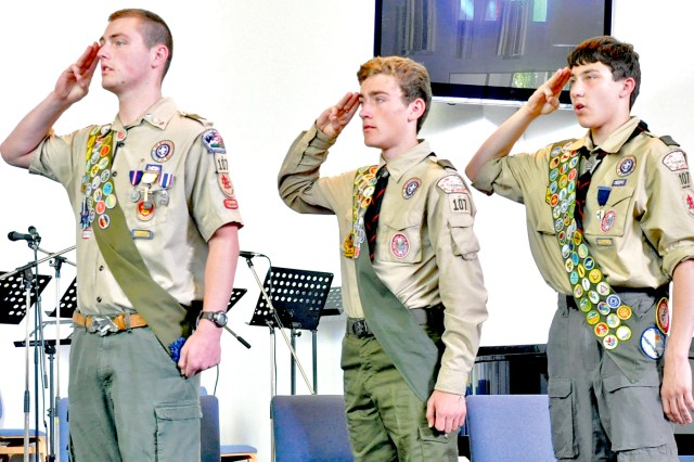 Troop 107 Boy Scouts Eli Kraft (from left), Nate Gerber and Brian Welch salute during their Eagle Scout Court of Honor ceremony June 4 at Wiesbaden's Hainerberg Chapel.