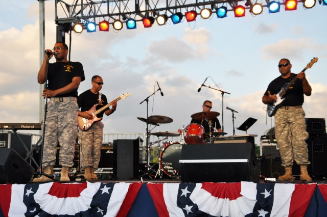 94th Army Rock Band's first of two rock bands performing.  From left, lead singer Staff Sgt. Justin Wade, guitarist 1st Sgt. Dewell Narvaez, drummer Sgt. Paul Amenta, and bass guitarist Staff Sgt. Michael Lazarus.
