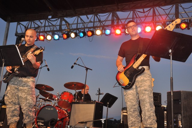 Second of two rock bands from the 94th Army Band performing. From left, Sgt. Mark Bilotta on the guitar, Staff Sgt. David Kuzminski on the drums, and Spc. Alexander Bowyer on the guitar.