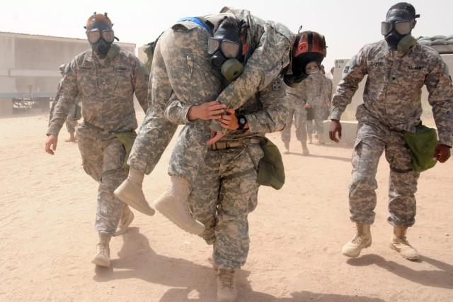 Pfc. Ronald Campos, healthcare specialist, Company B, 1st Battalion, 22nd Infnatry Regiment, 1st Armored Brigade Combat Team, 4th Infantry Division, carries simulated casualty Sgt. Christpher Clover, a wheeled vehicle mechanic, to the Brigade Aid Station after a indirect fire drill at Camp Buehring, Kuwait, June 5, 2013. (U.S. Army photo by Spc. Andrew Ingram, 1st ABCT PAO, 4th Inf. Div.)