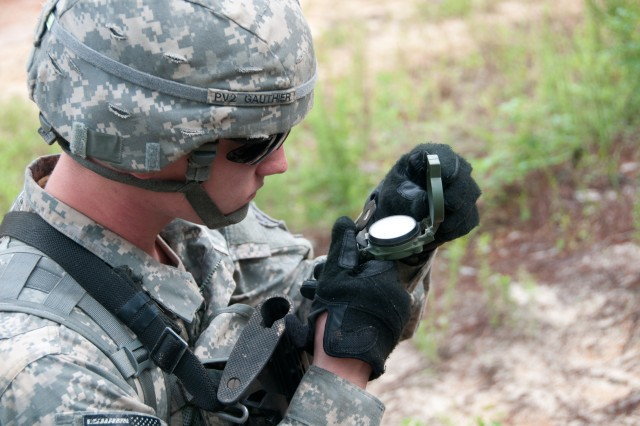 A paratrooper with the 82nd Airborne Division's 1st Brigade Combat Team uses a lensatic compass to find his way to his next point during land navigation testing at Fort Bragg, N.C., June 9, 2013. Land navigation is one of the seven major events that must be passed in order to earn the coveted Expert Infantryman Badge. (U.S. Army photo by Staff Sgt. Jonathan A. Shaw)