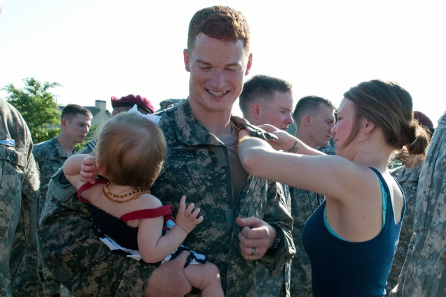Spc. Collin J. Cirrone, an infantryman with the 82nd Airborne Division's 1st Brigade Combat Team, smiles at his 1-year-old daughter, Limdley, as his wife, Candace, pins an Expert Infantryman Badge onto his uniform, June 13, 2013, at Fort Bragg, N.C. Cirrone was one of only 42 candidates out of an original 486 to earn the coveted badge after a week of events including an Army Physical Fitness Test, day and night land navigation, weapons employment, infantry skills testing lanes and a 12-mile road march. (U.S. Army photo by Staff Sgt. Mary S. Katzenberger)