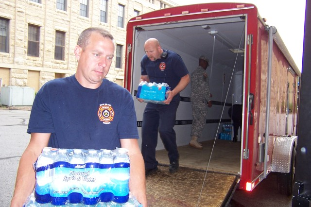 Rock Island Arsenal Firefighters unload 110 cases of water on June 13. The water was collected by the Davenport Fire Department's Military Appreciation Month Water Drive for the local United Service Organization.