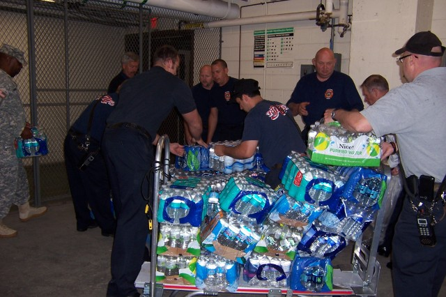 Firefighters from Rock Island Arsenal Fire Department are hard at work stacking donated water for the United Service Organization on June 13. The water was collected during Military Appreciation Month by the Davenport Fire Department.