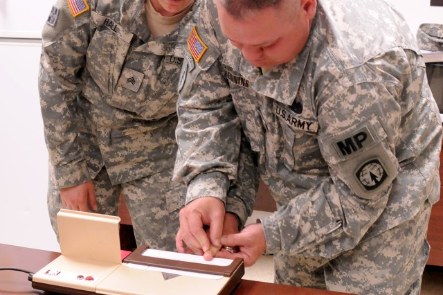 Staff Sgt. Mike Henning fingerprints Sgt. Heather Hall June 4 during a Guardian Academy class. The fingerprints are entered into their system to eliminate the MPs during cases requiring fingerprinting identification.