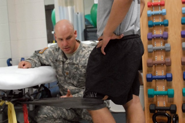 """Washington, Mo. native, Maj. Christopher Allen (left), a medical specialty corps officer and brigade physical therapist, observes Spc. David Arriba, a San Antonio native and geospatial engineer, both assigned to the 1st """"Ironhorse"""" Brigade Combat Team, 1st Cavalry Division, performs a terminal knee extension using a Thera-band June 12 at Harvey Physical Fitness Center's Physical Therapy Office at Fort Hood, Texas. The exercise is used to promote hip and lower-extremity strength and control. (Photo by Staff Sgt. John Couffer, 1st BCT Public Affairs, 1st Cav. Div.)"""
