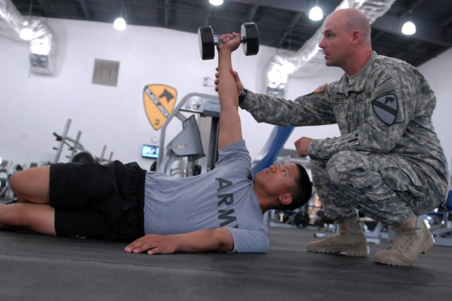 "Washington, Mo. native, Maj. Christopher Allen (right), a medical specialist corps officer and physical therapist, instructs San Antonio native, Spc. David Arriba, a geospatial engineer, both assigned to the 1st ""Ironhorse"" Brigade Combat Team, 1st Cavalry Division, on how to properly perform an ""arm bar"" physical therapy exercise June 12 at Harvey Physical Fitness Center at Fort Hood, Texas. The exercise is used to promote shoulder strength, flexibility and stability. (Photo by Staff Sgt. John Couffer, 1st BCT Public Affairs, 1st Cav. Div.)"