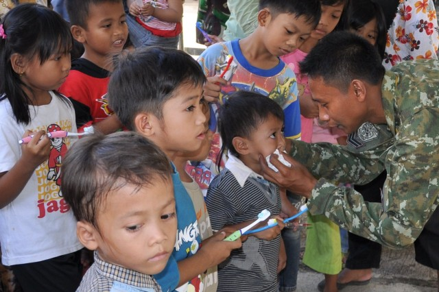 A Tentara Nasional Indonesia medic helps teach local children dental hygiene during a free public health day provided to the community at the Kostrad Medical Clinic in Cilodong, Indonesia, June 19, 2013. The public health day was held at the close of Garuda Shield 13, a U.S. Army Pacific-sponsored bi-lateral exercise between the U.S. Army and the Tentara Nasional Indonesia Army, which focused on developing the respective militaries' ability to contribute to United Nations peace support.