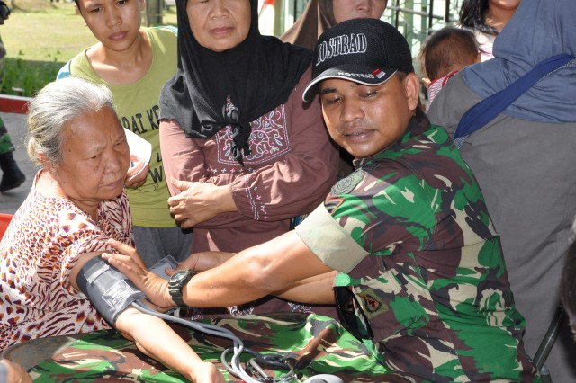 Tentara Nasional Indonesia medic Sgt. Iskandar takes vital signs of local resident Rodiah, 65, during a free public health day provided to the community at the Kostrad Medical Clinic in Cilodong, Indonesia, June 19, 2013. Rodiah learned she has high blood pressure and received medication. More than 200 residents received medical screenings and treatment throughout the day. The public health day was held at the close of Garuda Shield 13, a U.S. Army Pacific-sponsored bi-lateral exercise between the U.S. Army and the Tentara Nasional Indonesia Army, which focused on developing the respective militaries' ability to contribute to United Nations peace support.