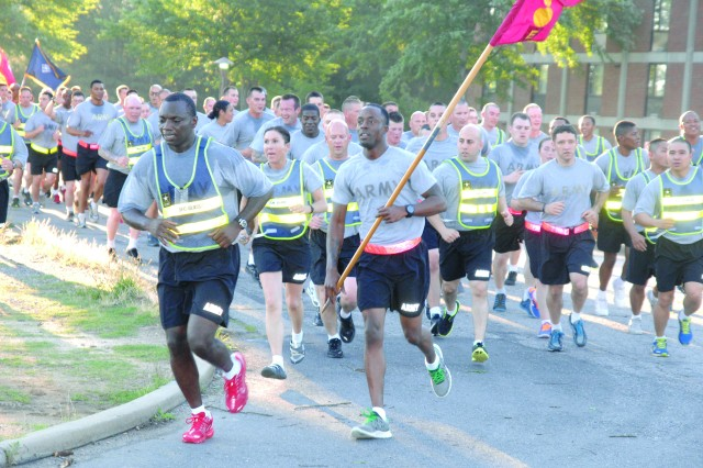 Sgt. 1st Class Tony Glass runs at the front of the Echo Company, 832nd Ordnance Battalion, formation during Fort Lee's Army Birthday Run Friday. (LEFT) A Quartermaster School advanced individual training student shows her enthusiasm during the run.