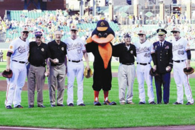 """Baltimore Oriole Tommy Hunter, retired Col. Douglas Dillard, retired Col. Bert Rice, Oriole Brian Matusz, the Oriole Bird, retired Sgt. Maj. Ray Moran, Oriole Troy Patton, Garrison Commander Col. Edward C. Rothstein and Oriole T.J. McFarland pose for a photo during Fridayâ,""""s Military Appreciation Day at Oriole Park at Camden Yards. Rothstein and the three retired Soldiers simultaneously threw out the first pitch."""