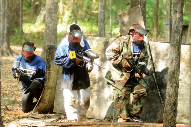 From left to right, Julia Botello, Elijah Moffett and Kyle Brown push forward to an enemy position Wednesday at the Woodlands Paintball Area.