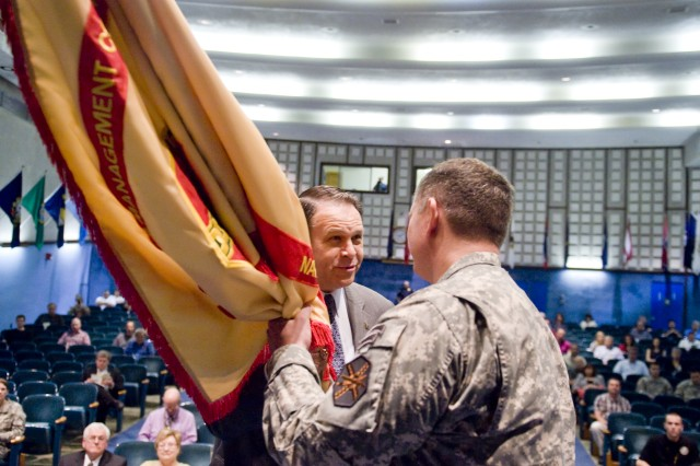 Mr. Davis Tindoll, Atlantic Region Director of the U.S. Army Installation Management Command passes the colors to Lt. Col. Brian Greata signifiying the change of command of the U.S. Army Garrison Natick.