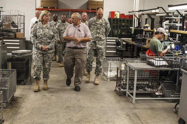 Anniston Army Depot Weapons Division Chief Jeff Bonner, center, guides Army Materiel Command Deputy Commanding General Lt. Gen. Patricia McQuistion through the installation's Small Arms Repair Facility. Pictured at the right of the group is Depot Commander Col. Brent Bolander.