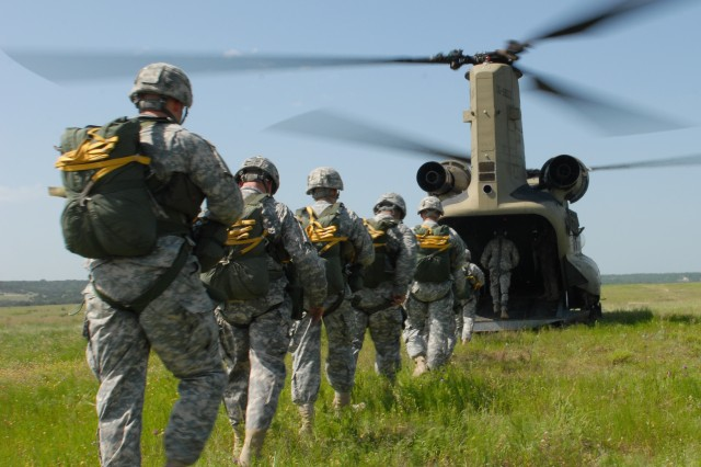 """Paratroopers make their way to a CH-47 Chinook helicopter at Rapido Drop Zone prior to a """"Hollywood"""" proficiency jump.  The Paratroopers, assigned to C Co, 2-38 Cavalry, 504th BFSB, take part in a static line jump June 19 at Fort Hood. The jump was part of an annual requirement for all Paratroopers to maintain a minimum proficiency of at least one jump per quarter. Families were on hand to get a first hand glimpse of an Airborne operation."""