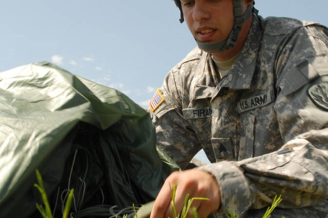 Sergeant Emilian Firan, a Chemical, Biological, Radiological and Nuclear NCO with C. Company, 2-38 Cavalry 504th BFSB, works to repack his chute following his successful completion of a static line jump June 19 at Fort Hood.
