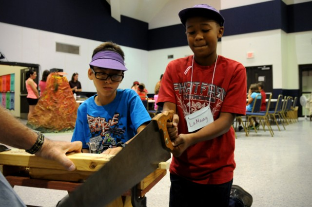 LaMaray Moultrie, VBS student, saws a piece of wood to create a dradle as his friend, Alex Villa, watches at vacation Bible school at the Spiritual Life Center June 13.