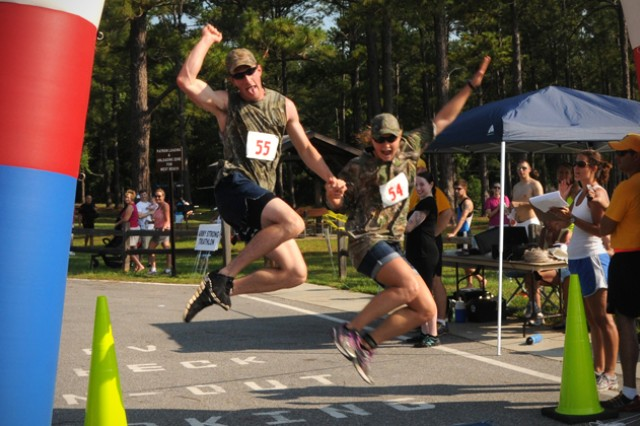 Garrett and Kristen Wilson cross the finish line to cheers from the crowd during the 2013 Fort Rucker Army Strong Triathlon at West Beach on Lake Tholocco June 15. More than 20 three-man relay teams and more than 190 individuals participated in the race.
